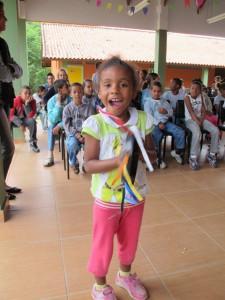 Aluna mostra habilidade ao tocar o pandeiro que ela mesma fez.